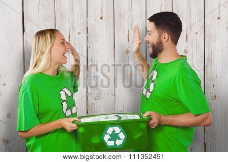 Smiling volunteer doing high five while holding container against wooden background