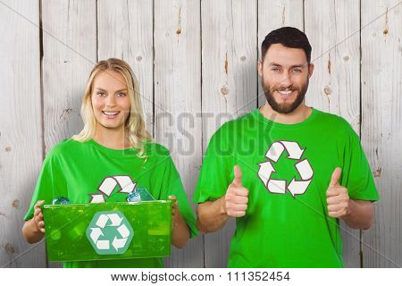 Portrait of cheerful volunteers in recycling symbol tshirts against wooden background