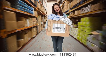 Portrait of a young woman with clothes donation against worker with trolley of boxes