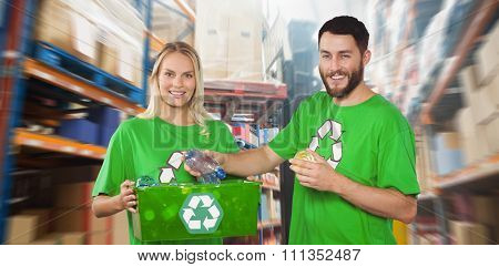 Portrait of happy man holding bottle against focused driver operating forklift machine