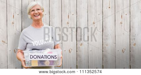 Happy grandmother holding donation box against wooden background