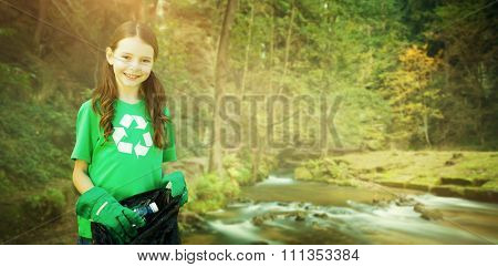 Happy little girl collecting rubbish against rapids flowing along lush forest