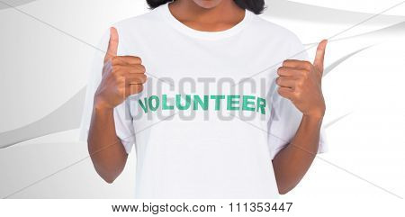 Woman wearing volunteer tshirt and giving thumbs up against white wave design