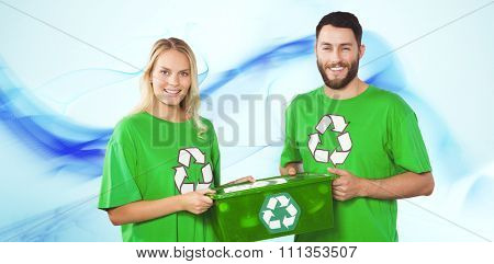 Portrait of smiling volunteers carrying recycling container against blue abstract design