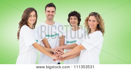 Smiling volunteer group piling up their hands against green vignette