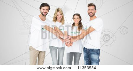 Group portrait of happy volunteers with hands together against interface with graphs