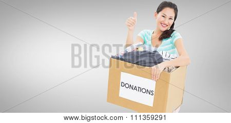 Woman with clothes donation gesturing thumbs up against grey vignette