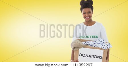 Smiling young woman with clothes donation against yellow vignette