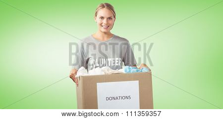 Portrait of beautiful woman holding clothes donation box against green vignette