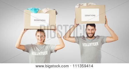 Portrait of volunteers carrying donation boxes on head against grey vignette