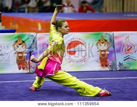 JAKARTA, INDONESIA - NOVEMBER 17, 2015: Liudmyla Temna of Ukraine performs the movements in the women's Compulsory Changquan event at the 13th World Wushu Championship 2015 in Istora Senayan Stadium.