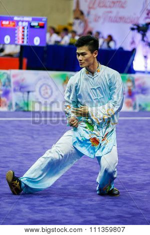 JAKARTA, INDONESIA - NOVEMBER 17, 2015: Jack Chang Loh of Malaysia performs the movements in the men's Compulsory Taijiquan event at the 13th World Wushu Championship 2015 in Istora Senayan Stadium.