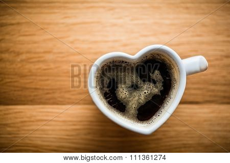Black coffee, espresso in heart shaped cup. Love concept, Valentine's Day. View from the top, vintage