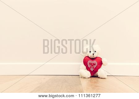 Cute teddy bear with big red plush heart. Sitting on wooden floor against white wall. Rustic style, vintage. Love, valentine's day.
