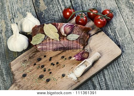 Smoked pork with herbs and spices on wooden board