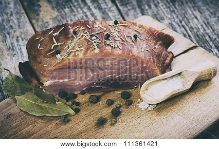 Smoked pork with herbs and spices on wooden board.