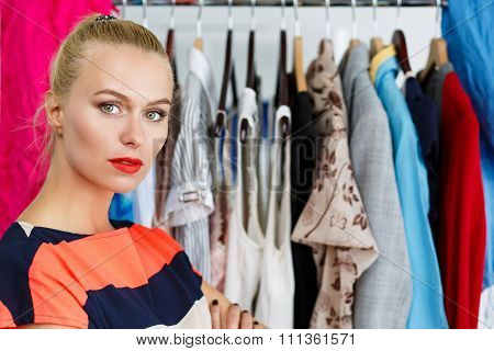 Thoughtful Sad Beautiful Blonde Woman Standing Near Wardrobe Rack Full Of Clothes