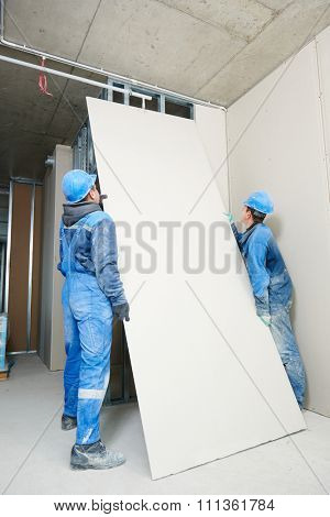 gypsum plasterboard installation during indoor walling by workers