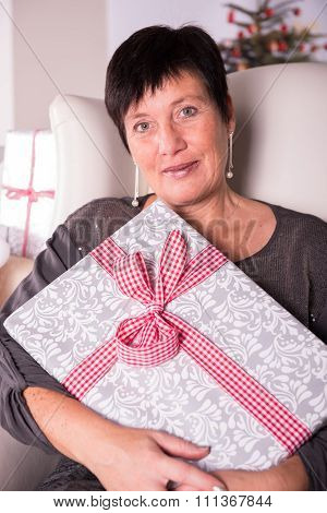 Portrait Happy Woman With Christmas Gift In Armchair
