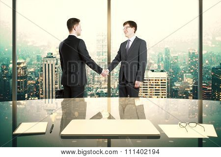 Business Partners Shake Hands In Modern Office With Night Megapolis City View