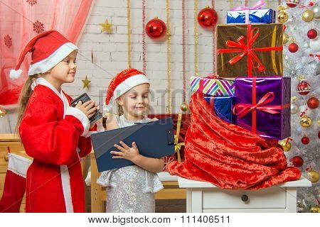 Santa Claus And Assistant Recount Gifts In A Bag