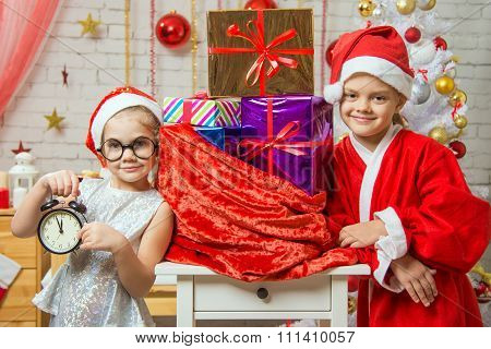 Girl Shows On The Clock, A Girl Dressed As Santa Claus Is Standing At The Bag With Gifts