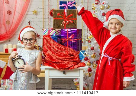 A Girl Holding A Clock, A Girl Dressed As Santa Claus Is Standing At The Bag With Gifts
