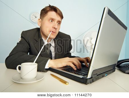 Businessman Drinks Coffee Through A Straw And Work In Internet