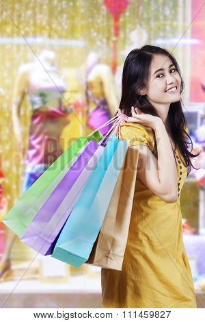 Cheerful Woman Holds Christmas Shopping Bags At Mall