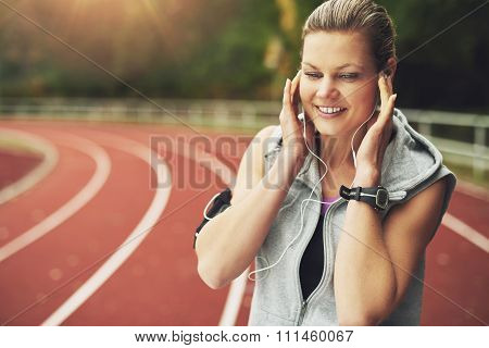 Smiling Woman Listening To Music On Track Field