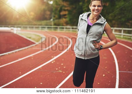 Fit Woman Smiling At Camera While Stretching