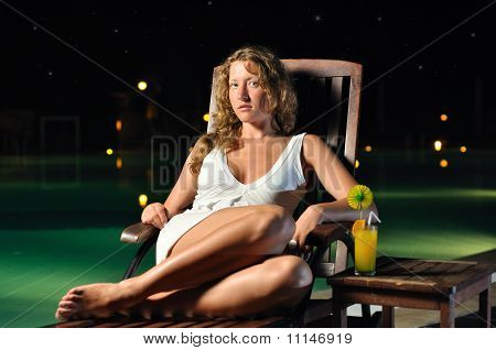 Sensual Woman Is Sitting On Chair At Poolside At Night And Looking At Camera