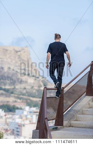 Back View Of Young Athlete Walking On Railing