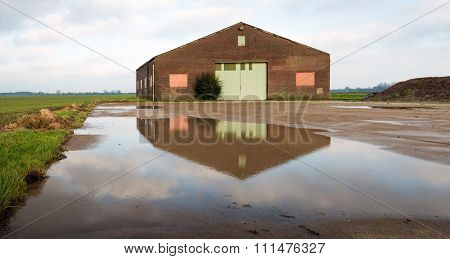 Old Barn Reflected In A Puddle Of Water