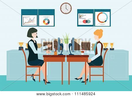 Two Business Woman Sitting At The Table.