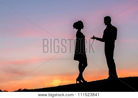 Guy doing the proposal for girl against a beautiful sky.