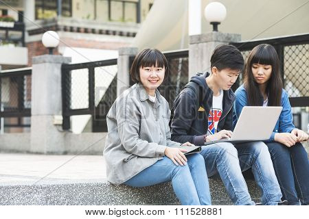 Happy group of students sitting at the park talking