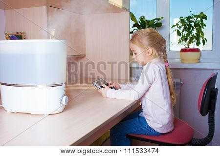 Little Girl With Tablet Pc Sitting Near Humidifier