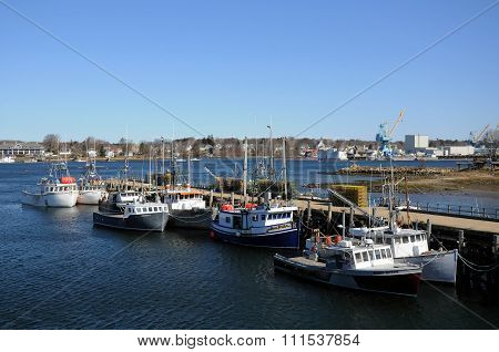 Fishing boats resting along side a dock