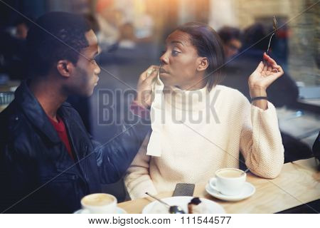 Young man and woman relaxing in coffee shop in cold winter day