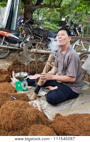 Man Smoking Tobacco In Large Pipe.