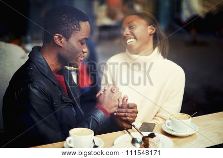 Cheerful woman sitting with her boyfriend in modern cafe bar during coffee break