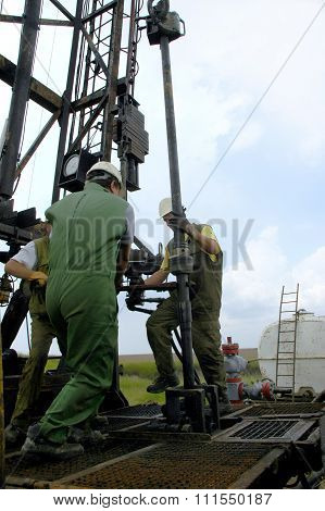 Workers work in the field on the oil and gas boring investigation