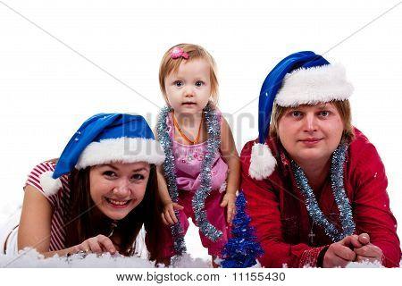 Family In Santa's Hat Lying In Artificial Snow