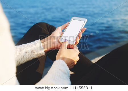 Female chatting on-line on cell telephone while sitting on pier near sea