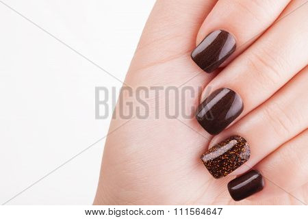 Brown nail polish on the nails.
