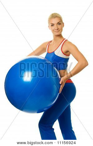 Happy young trainer holding a fitness ball