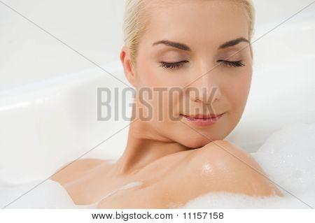 Young beautiful woman washing in a bathroom