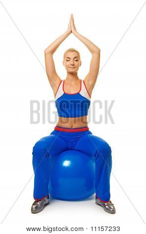 Beautiful young woman doing yoga exercise on the fitness ball