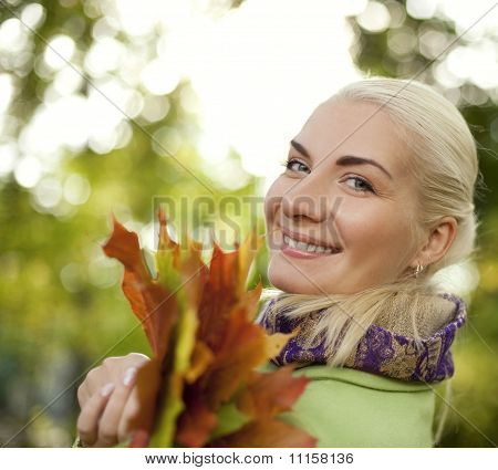 Woman with golden autumn leaves